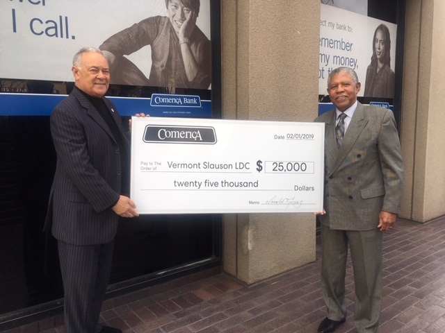 CEO Joseph Rouzan standing with $25,000 check from Comerica